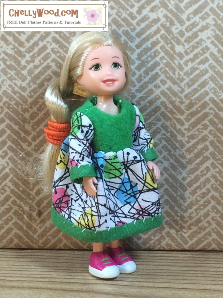 """A Kelly doll models an Easter dress with a felt bodice and cotton sleeves and a cotton skirt. The sleeves and skirt are trimmed with bias tape. This gives the impression that the sleeves have cuffs. The watermark says """"Chelly Wood dot com Free doll clothes patterns and tutorials."""""""