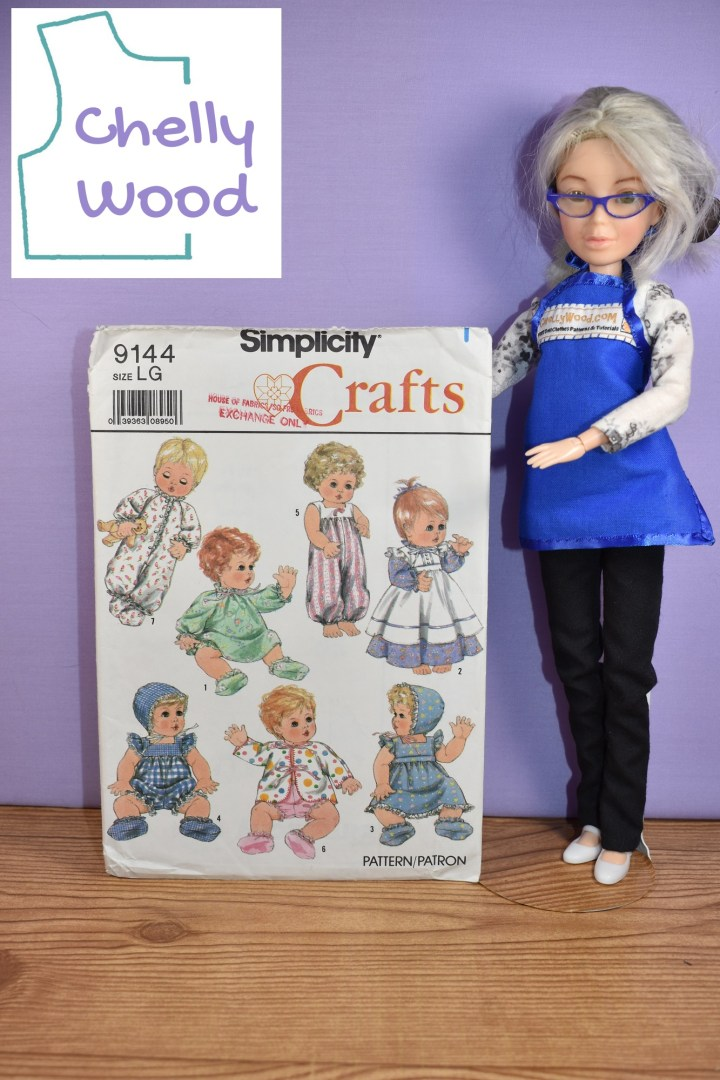 In this image, we see the Chelly Wood doll holding up Simplicity doll clothes craft pattern #9144 for baby dolls. It says on the outside of the pattern that this is a craft pattern for large baby dolls. There's a discussion about the use of ribbons with this pattern at ChellyWood.com