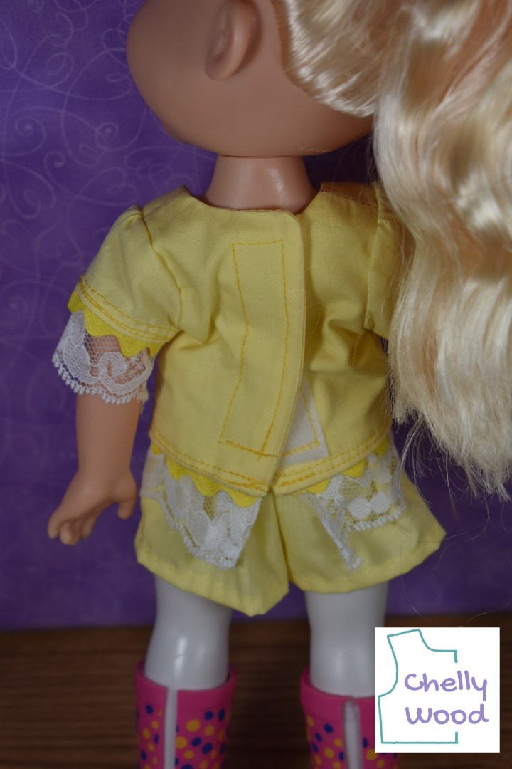 In this image, we see that a Disney Princess Elsa Toddler doll is wearing a handmade shirt that has been sealed shut with Velcro sew-on strips at the back of the shirt, but the Velcro sticks out a little bit (unsealed) at the very bottom of the shirt, where the doll's hips are a little too wide to accommodate the Velcro closure. Had the sewist used snaps instead of Velcro, the closure would look more attractive. The watermark reminds us that the free printable PDF sewing patterns for making these doll clothes to fit Disney Princess Toddler dolls can be found at Chelly Wood dot com.