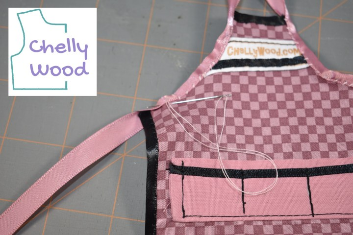 In this photo (which bears the watermark for ChellyWood.com) we see the side of an apron where a sewist is applying ribbon to create ties for the apron. The sewist has curved the ribbon around the raw edges of the apron's fabric and is using a whip stitch to secure the ribbon over the raw edge. The ribbon is being attached to the part of the apron that goes from the breastbone to the the underarm area, and the ribbon extends from the breastbone upward, to form the ribbon around the apron's neck. The same ribbon extends from the underarm area to outward at the apron's side, to form the ribbon tie at the back of the apron.