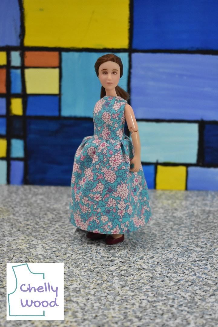 Standing in front of a wall-sized painting that imitates a stained glass window in different shades of blue and gold, we see a 1:12 scale Breyer Rider doll modeling a lovely long dress with round neckline and a gathered skirt. It's a sleeveless dress made of pale blue cotton with tiny pink and white flowers in an artistic style that reminds us of the 1950's. The watermark reminds us that you can download the free printable PDF pattern for this pattern to fit 1:12 scale fashion dolls at ChellyWood.com
