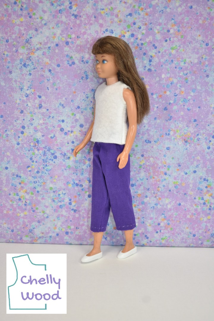 """In this photo, a vintage skipper is walking in front of a lavender and blue spotted background with a white floor. She wears purple ankle pants and a white felt sleeveless shirt. She also wears white plastic flats which are almost camouflaged against the white floor. The logo in the lower left corner says """"Chelly Wood,"""" reminding us that these doll clothes can be made using the free printable PDF doll clothes sewing patterns found at ChellyWood.com"""