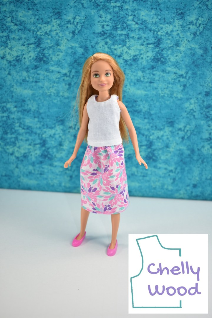 """In this image, we see a Mattel Stacie doll (Barbies little sister) wearing handmade doll clothes: a white tank top and a leaf-print cotton skirt with an elastic waist. The logo says """"Chelly Wood."""" The doll stands before a watery blue background with a slight smile. Her shoes are bright pink, like some of the leaves on her little skirt."""