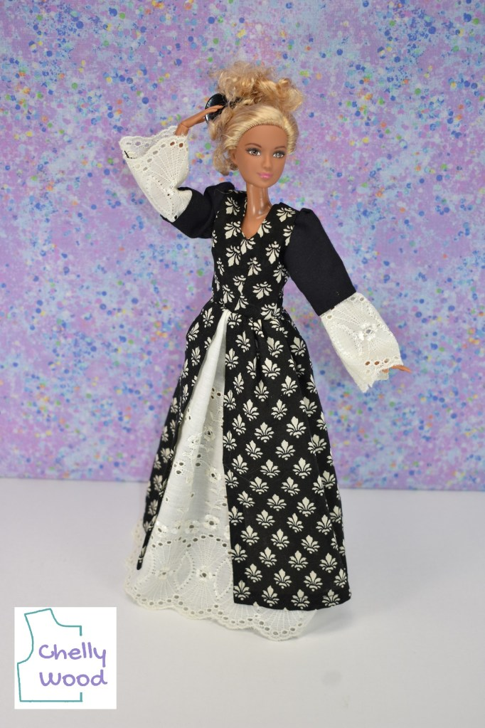 """A made-to-move Barbie models a Renaissance gown decorated with tiny fleur de lis patterns. She stands with one hand at her hair, where she wears a cute little blond messy bun. (There's also a clamp in her hair reminiscent of the combs women wore in their hair back in the 1600's or so.) She poses before a spackled lavender colored wall, and her dress, which is black with white embellishments sharply contrasts against this pretty background color. The watermark in the lower left corner of the photo says """"Chelly Wood."""""""