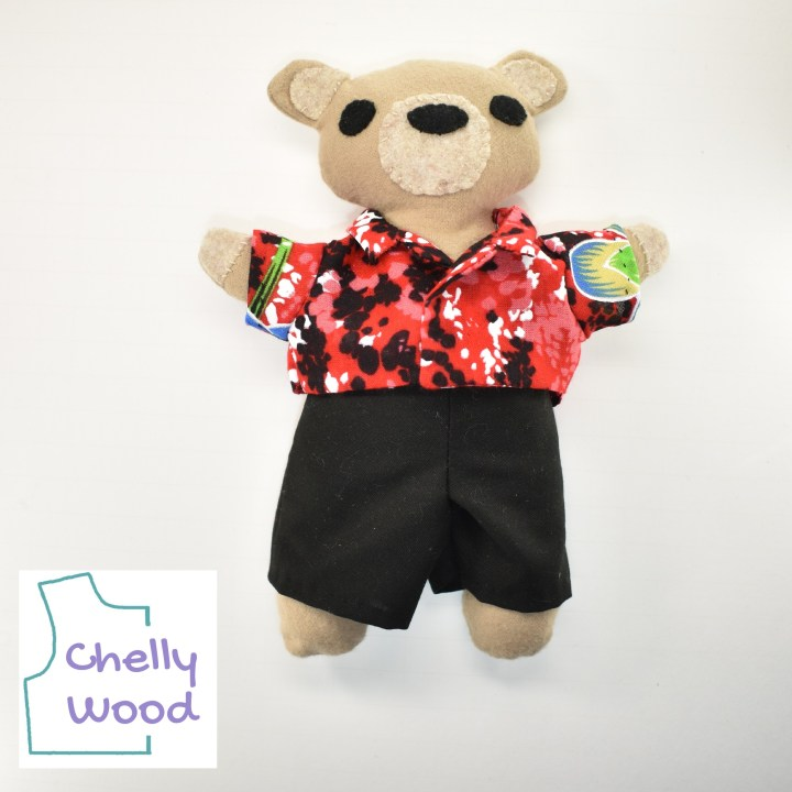 """Here we see a little tan bear made of flannel with felt eyes and a felt nose. His paws and ears also have felt. He wears a red, black, and white splotchy Hawaiian style shirt with a collar. He also wears black trousers. The watermark says, """"Chelly Wood."""""""