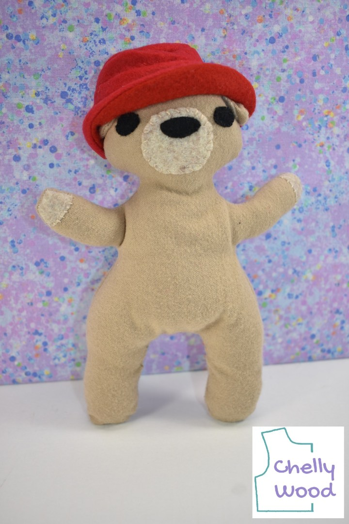 """A little tan bear wears a red felt hat. This bear is a plush toy that looks sort of like Paddington Bear. The watermark says, """"Chelly Wood."""""""