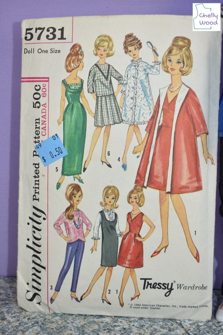 The image shows a close photo of Simplicity Tressy Doll Clothes Pattern 5731 (Copyright 1964). The doll clothes patterns offered in this pattern set include a long green ball gown with 1960's bodice style; a knife pleated skirt with a 3/4 length sleeve shirt; a pajama; a pair of pedal pusher pants with a 3/4 length sleeve shirt; a ruffled blouse with an American style jumper; a V-neck dress that goes above the knee; a swing coat with 3/4 length sleeves.