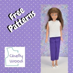 """A purple swatch of fabric with white dotted Swiss print forms a square. Inside the square is a vintage Skipper doll wearing handmade doll clothes (a shirt and pants) and the words """"free patterns"""" which are accompanied by the turquoise blue and purple logo for Chelly Wood dot com."""