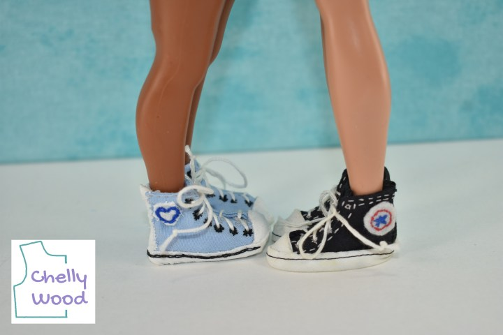 Two dolls face each other wearing handmade sneakers. The light blue Converse-like sneakers have a heart-shaped logo on the hi-top. The black sneakers have a more traditional blue star with red stitching, like true Converse shoes.