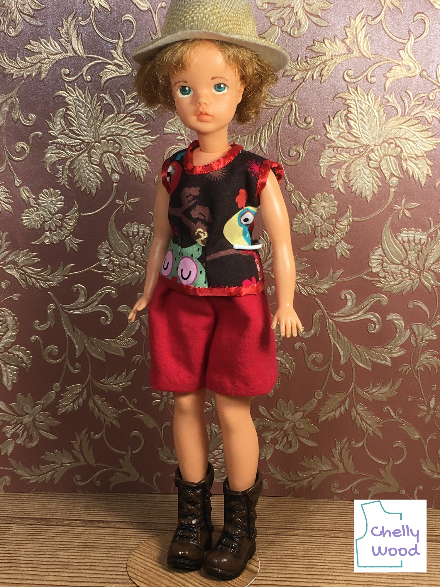 """In this photo, we see a vintage Tammy doll from Ideal Toy Corp. wearing a safari outfit or hiking gear, complete with a straw hat and little plastic boots. Her shorts are made of red flannel. Her shirt is cotton, trimmed in red ribbon. The overlay says, """"Chelly Wood"""" and indicates that the patterns and tutorials for making this outfit can be found at ChellyWood.com"""