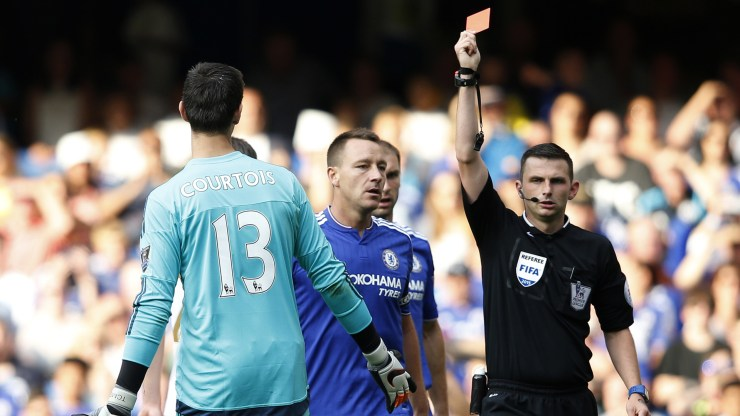 Referee Michael Oliver (R) shows the red card to send off Chelsea's Belgian goalkeeper Thibaut Courtois (L) after a foul on Swansea City's French striker Bafetimbi Gomis (unseen) conceeded a penalty as Chelsea's English defender John Terry (C) reacts during the English Premier League football match between Chelsea and Swansea City at Stamford Bridge in London on August 8, 2015. AFP PHOTO / ADRIAN DENNIS RESTRICTED TO EDITORIAL USE. No use with unauthorized audio, video, data, fixture lists, club/league logos or 'live' services. Online in-match use limited to 75 images, no video emulation. No use in betting, games or single club/league/player publications. (Photo credit should read ADRIAN DENNIS/AFP/Getty Images)