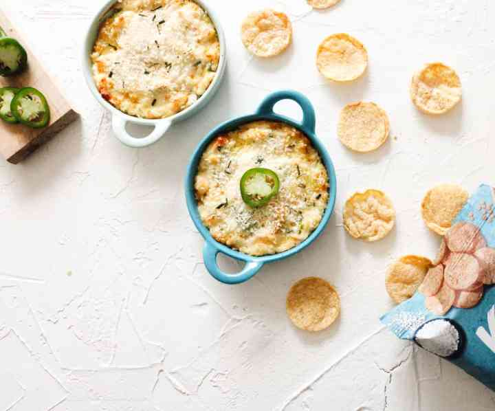 Vegan Jalapeno Dip in a blue and white bowl with chips scattered near it