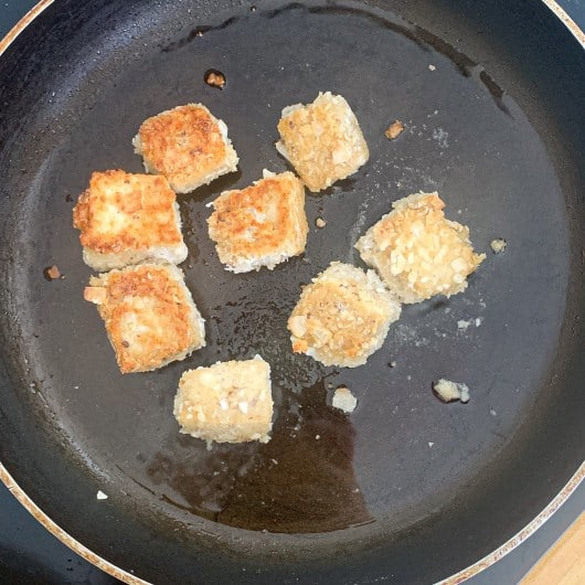 Tofu pieces in frying pan with oil. The top is golden brown.