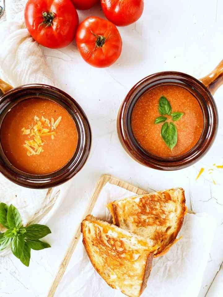 Creamy Vegan Tomato Soup in bowls with a grilled cheese sandwich and basil garnish