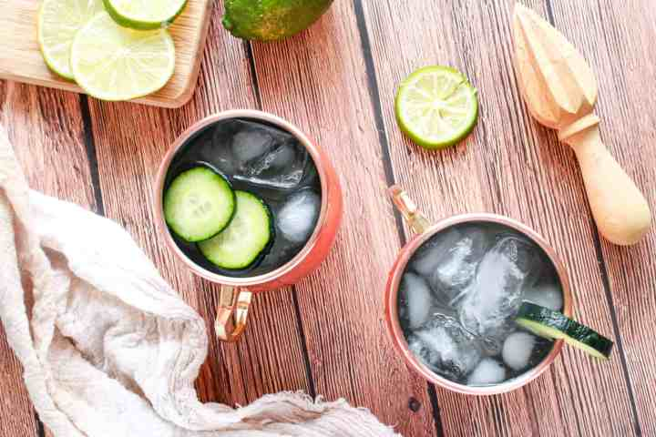 Flat lay of moscow mule with two mule glasses full of the cocktail and cucumber slices showing. Also there is a juicer and napking
