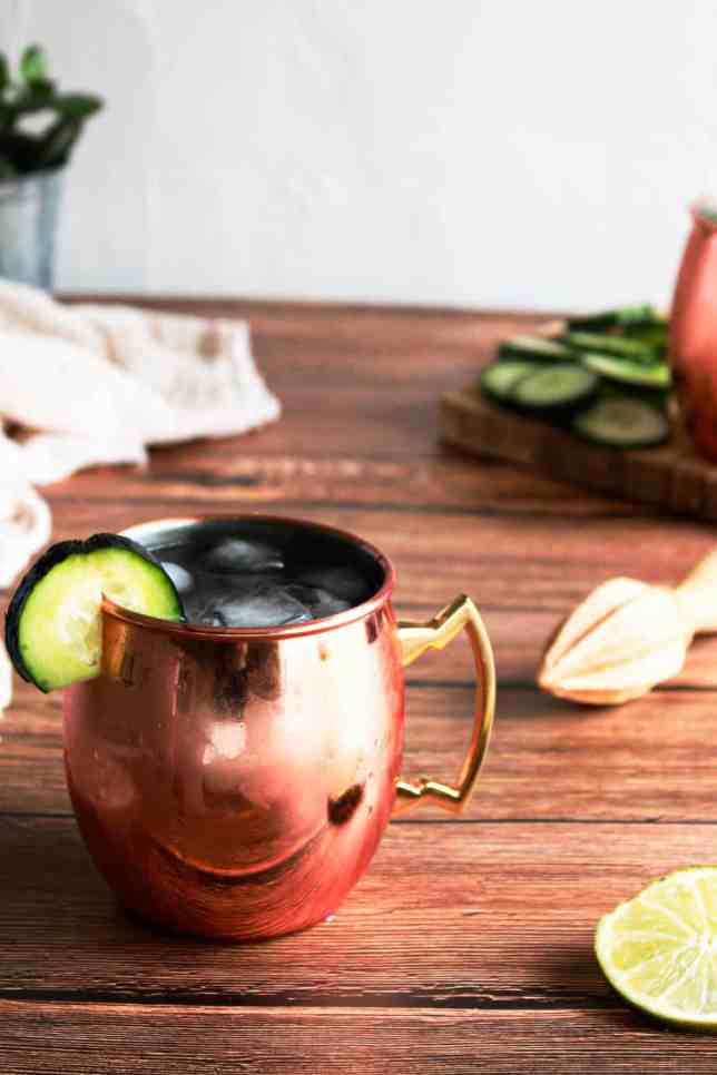 Cucumber Moscow Mule in a copper glass with a cucumber garnish. It is a wood surface with a lime and juicer next to it.