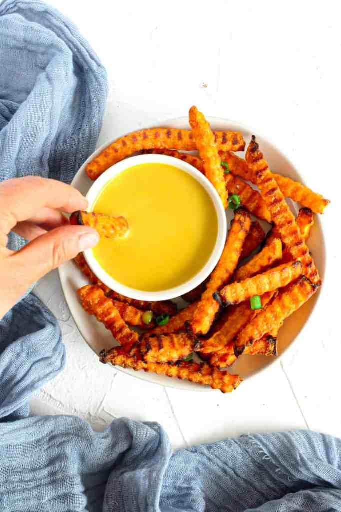 Air Fryer Sweet potato fries on a plate with honey mustard dipping sauce and the fry is being dunked into the sauce