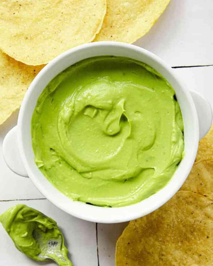 Creamy avocado dip in a white bowl on a textile surface with tortillas