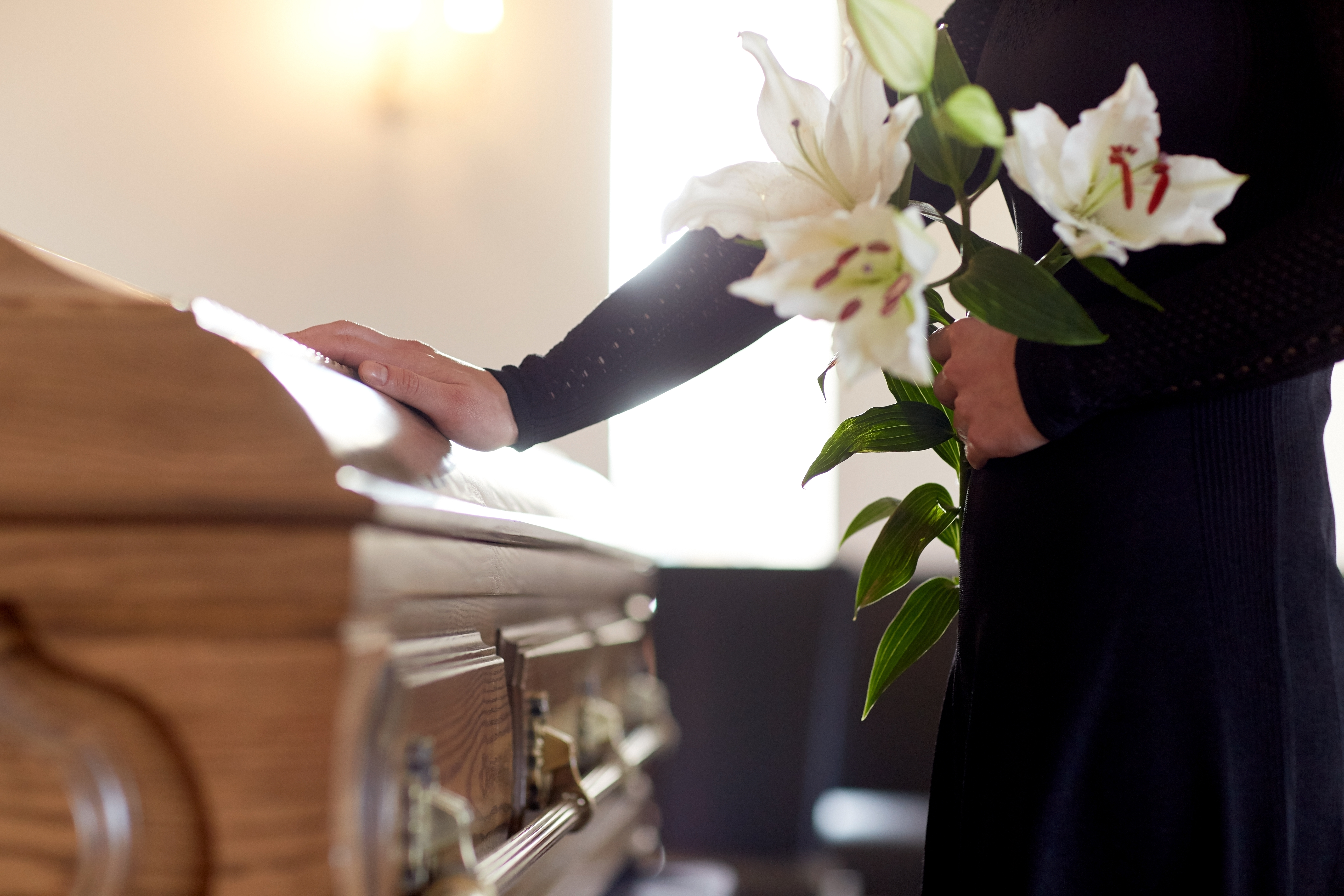 Woman standing at a casket with flowers in her hand
