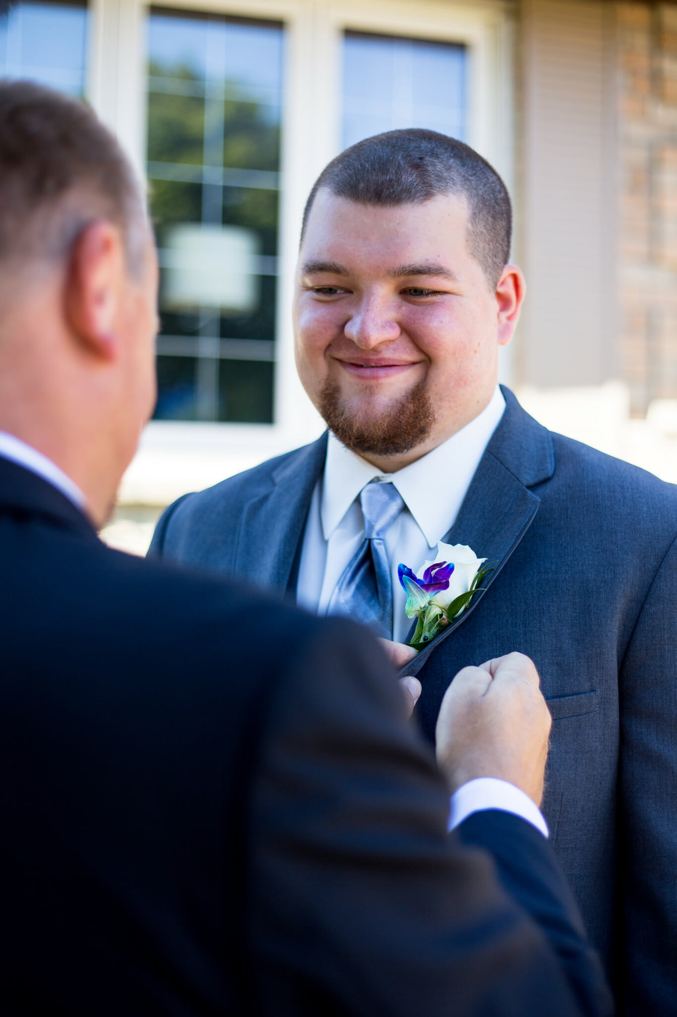 father putting on grooms boutonniere