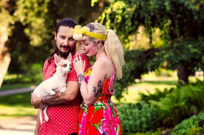 boyfriend holding dog while girlfriend looks at him