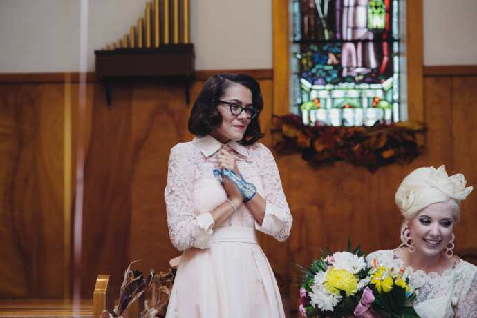 happy maid of honour watching couple sign marriage certificate
