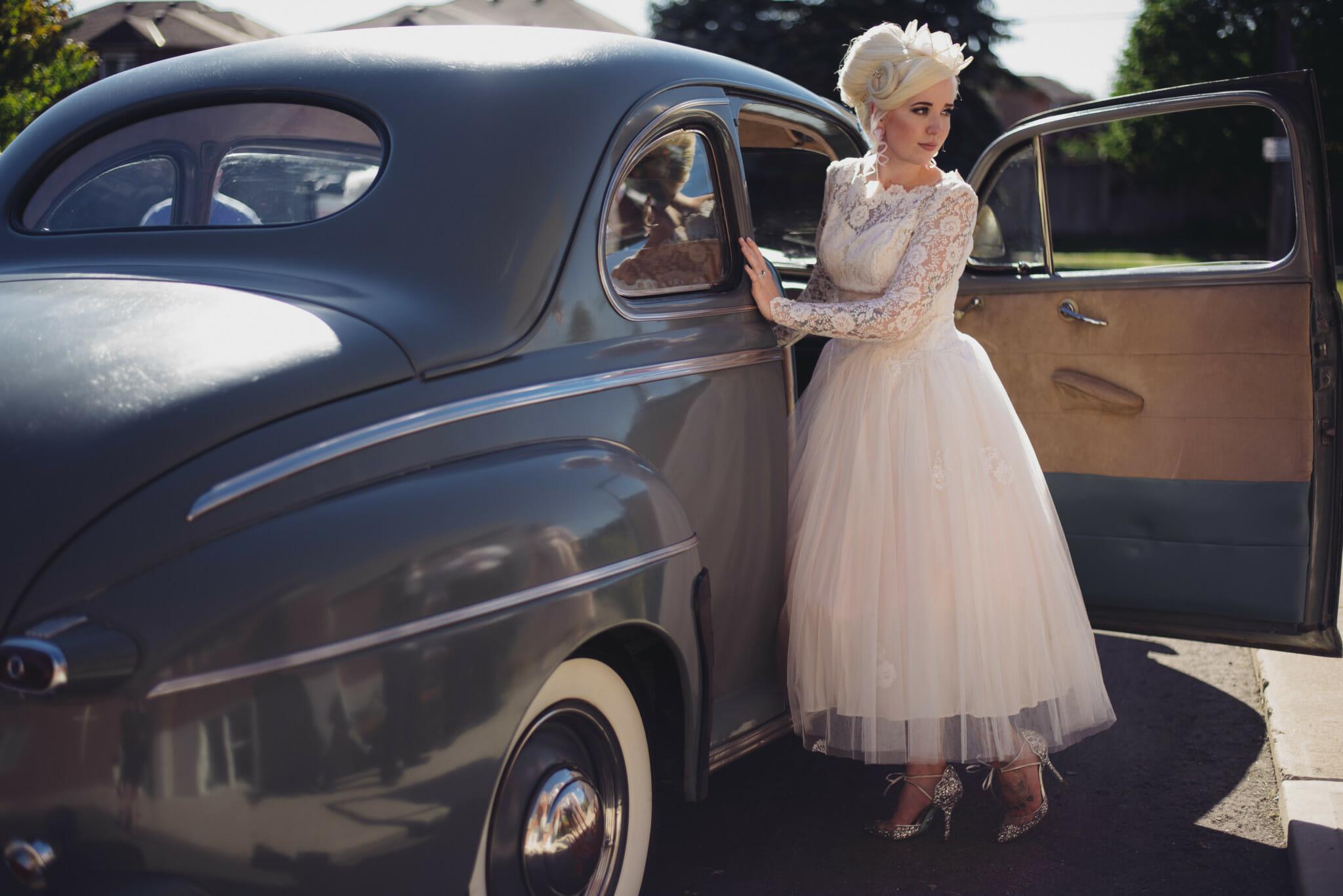 bride entering vintage car to go to parkwood