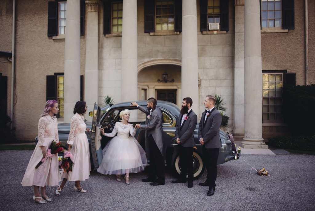 groom helps bride out of vintage car in front of parkwood