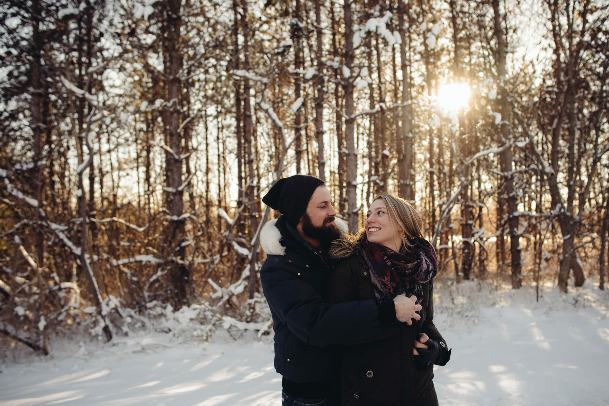 couple cuddle in front of trees at conservation area