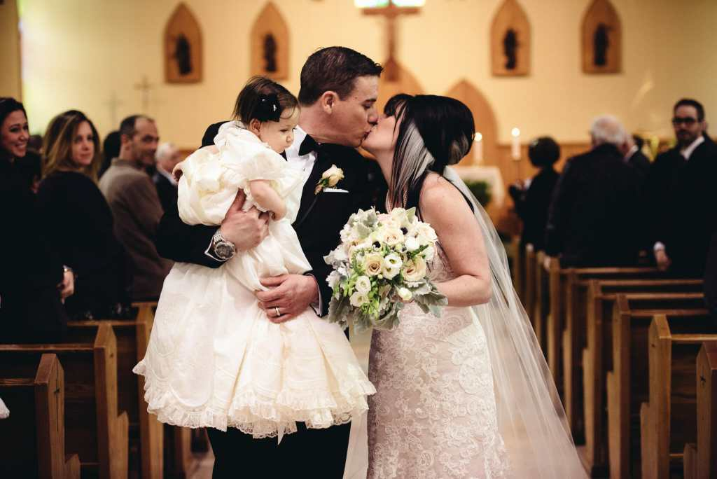 couple kiss after ceremony with daughter