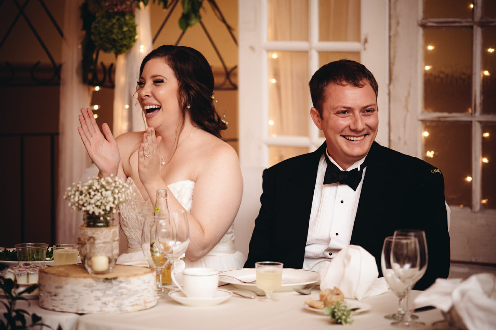 newlyweds laugh during speeches at st leo church wedding