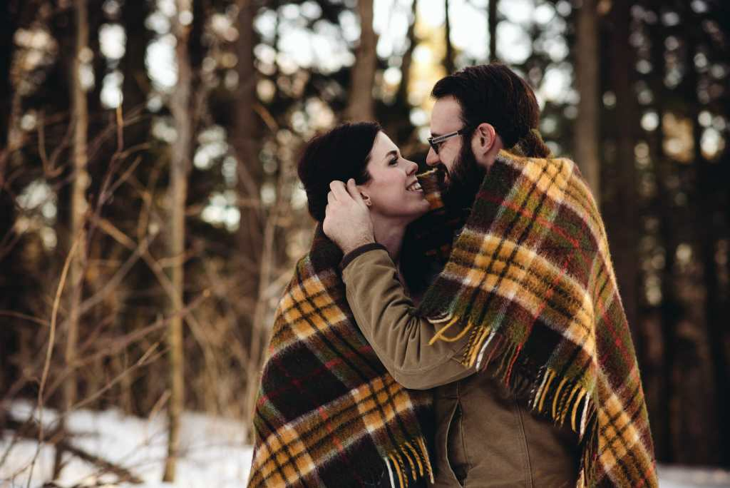 couple cuddles during engagement session bowmanville