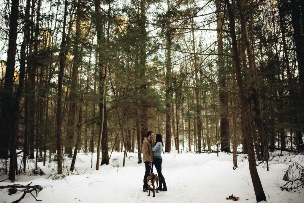 couple kisses in the forest with dog