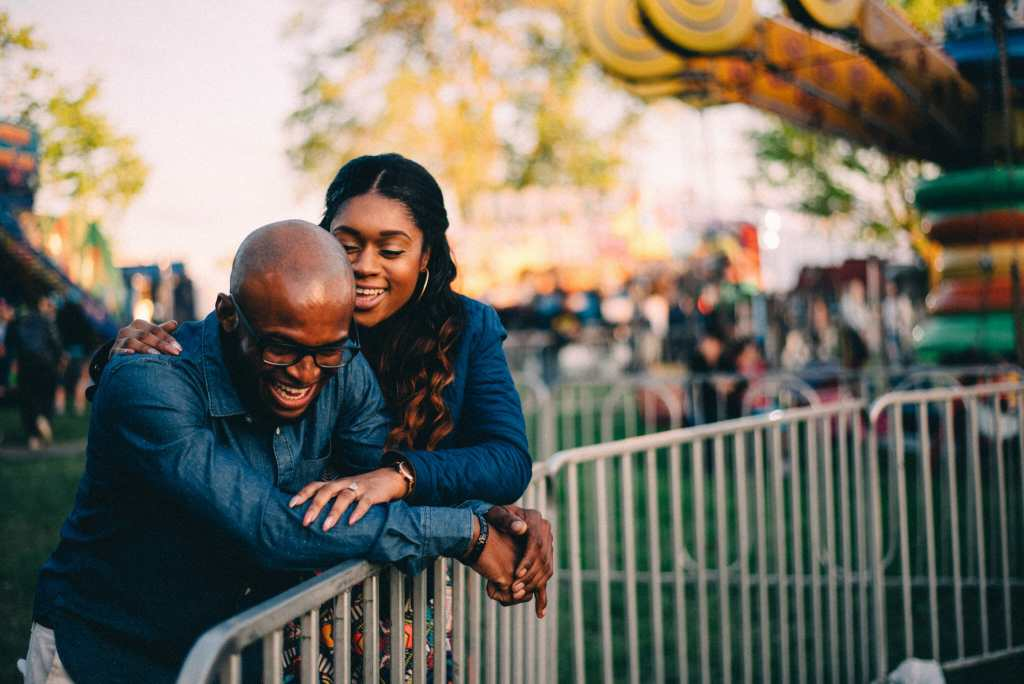 couple laugh while people watching at carnival