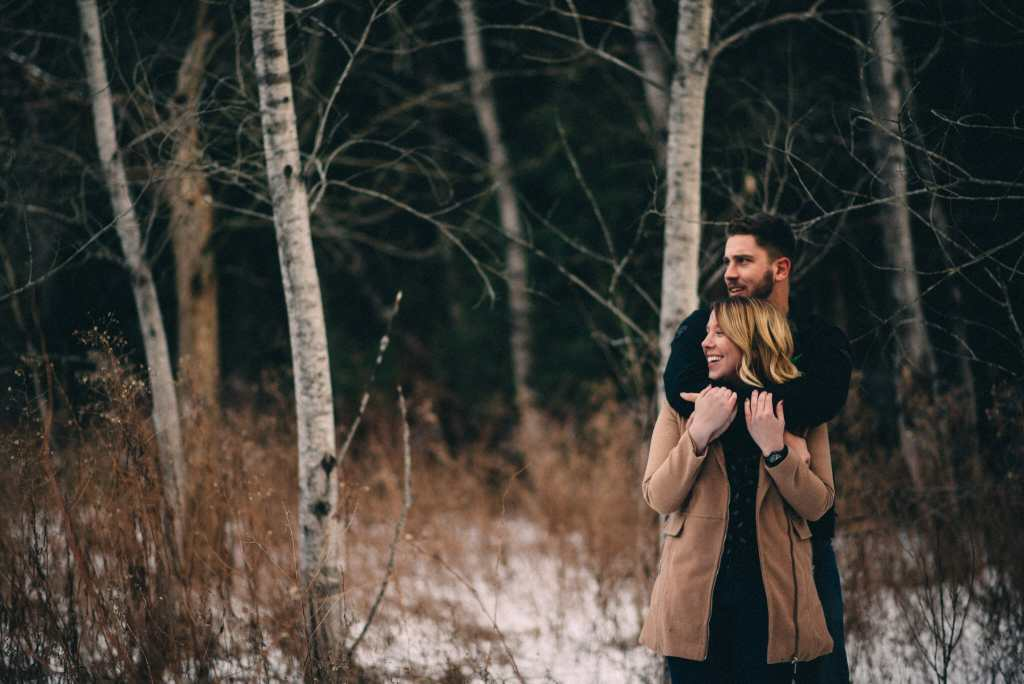 engaged couple snuggle in birch trees photos