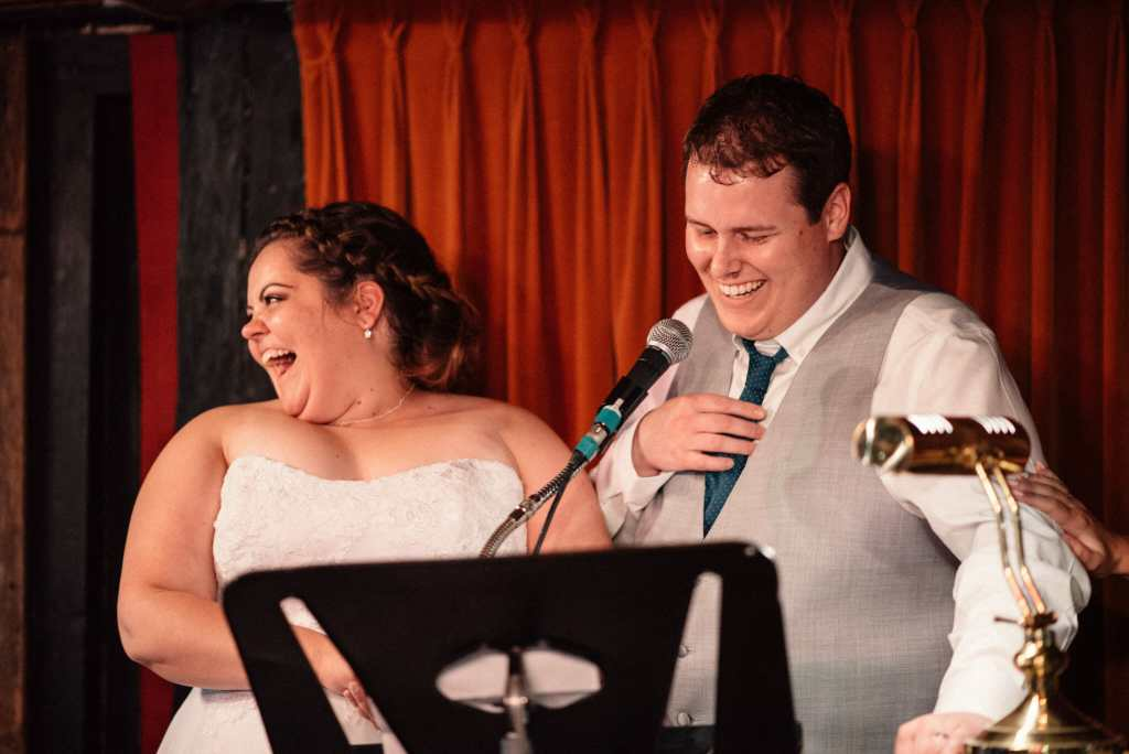 bride and groom laugh while giving speech at wedding reception