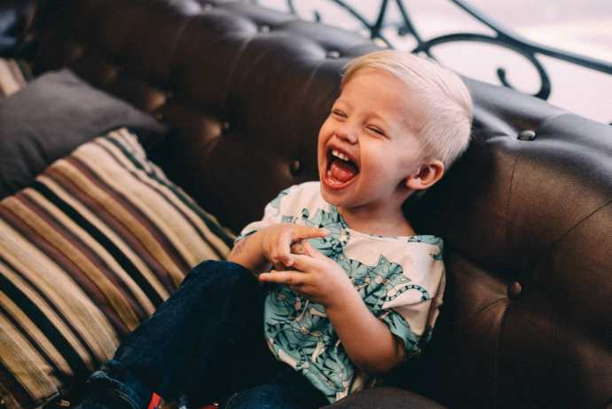 little boy laughs on couch at tattoo shop