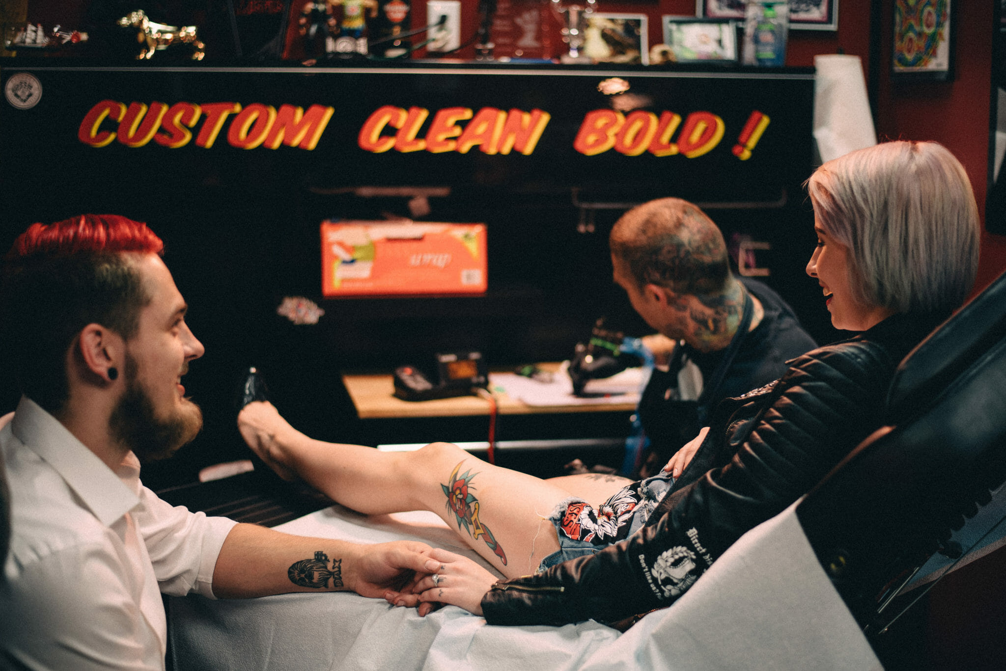engaged couple hold hands while getting matching tattoos