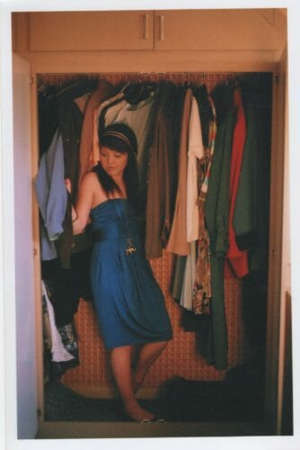 colour film portrait of girl in clothing closet