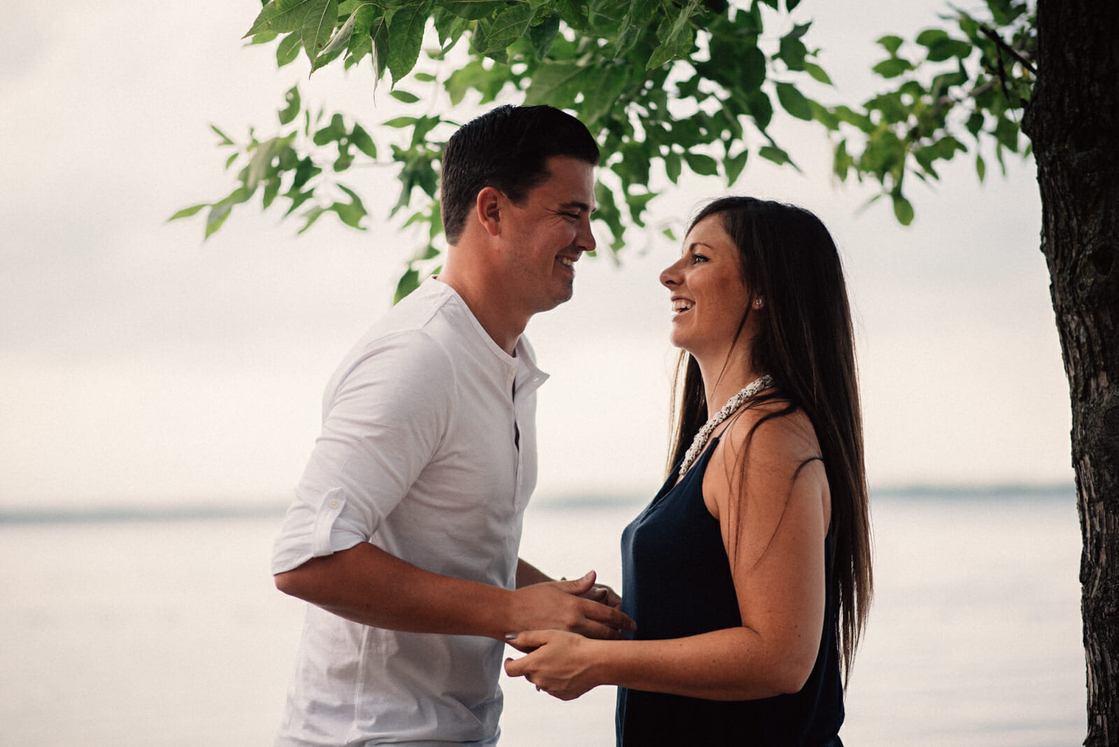couple laugh together during engagement session