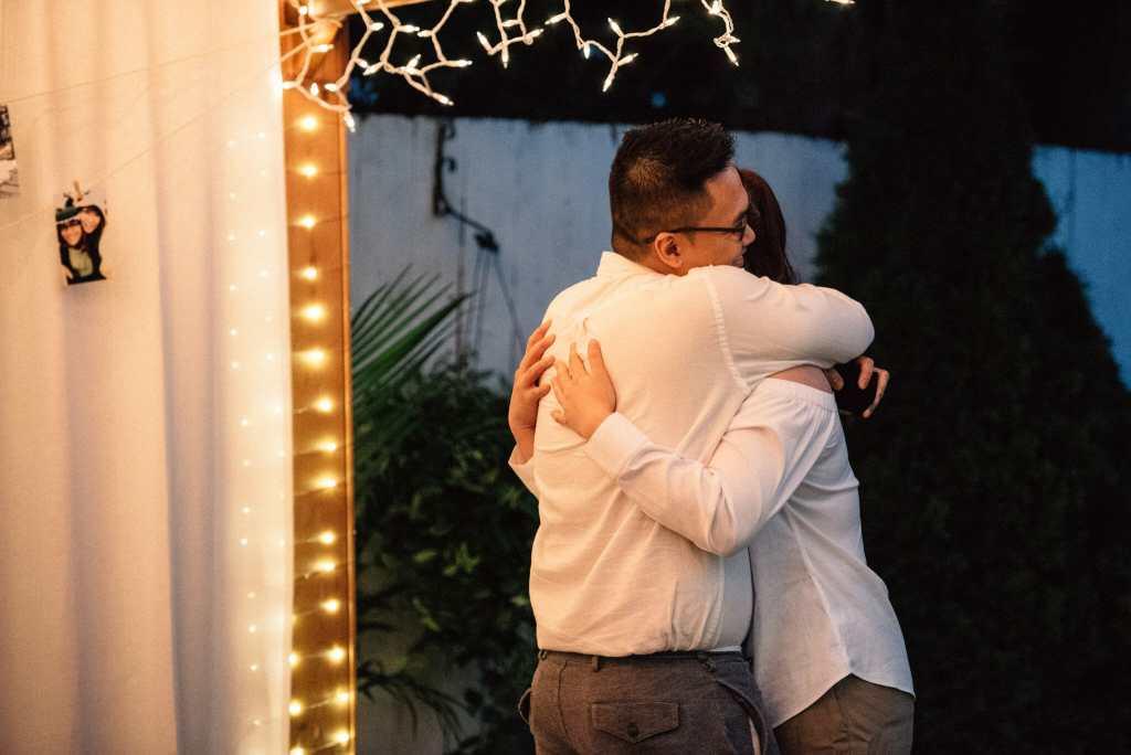 couple embraces after surprise engagement