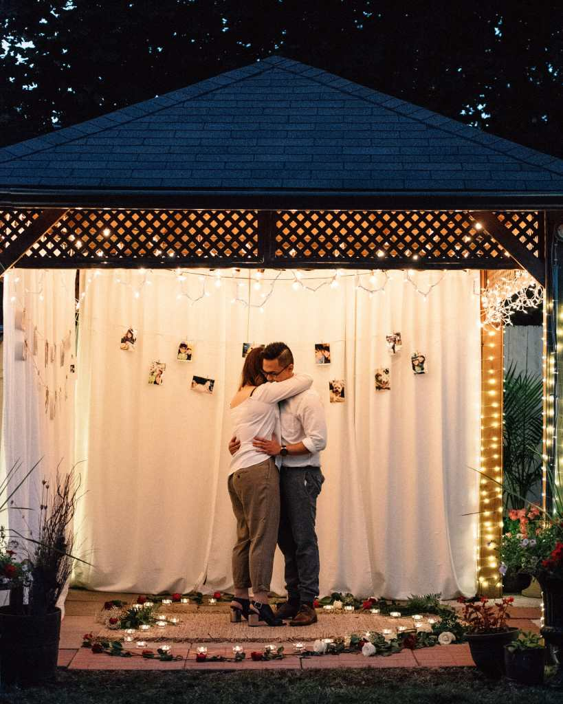 newly engaged couple slow dances in gazebo at night