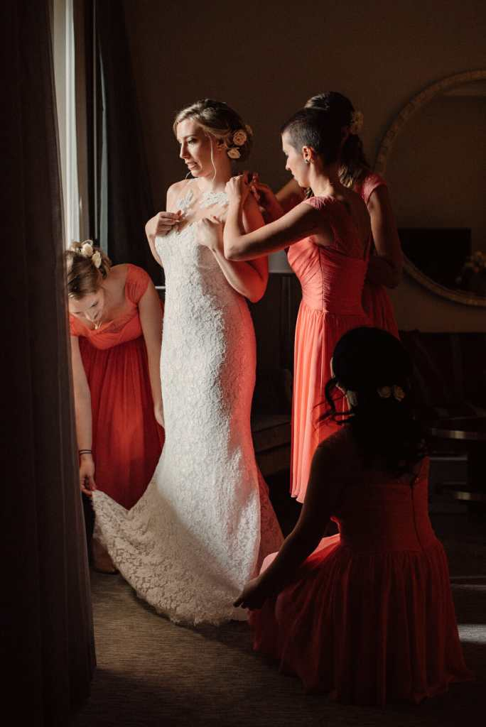 bride being helped to put on her wedding dress by bridesmaids