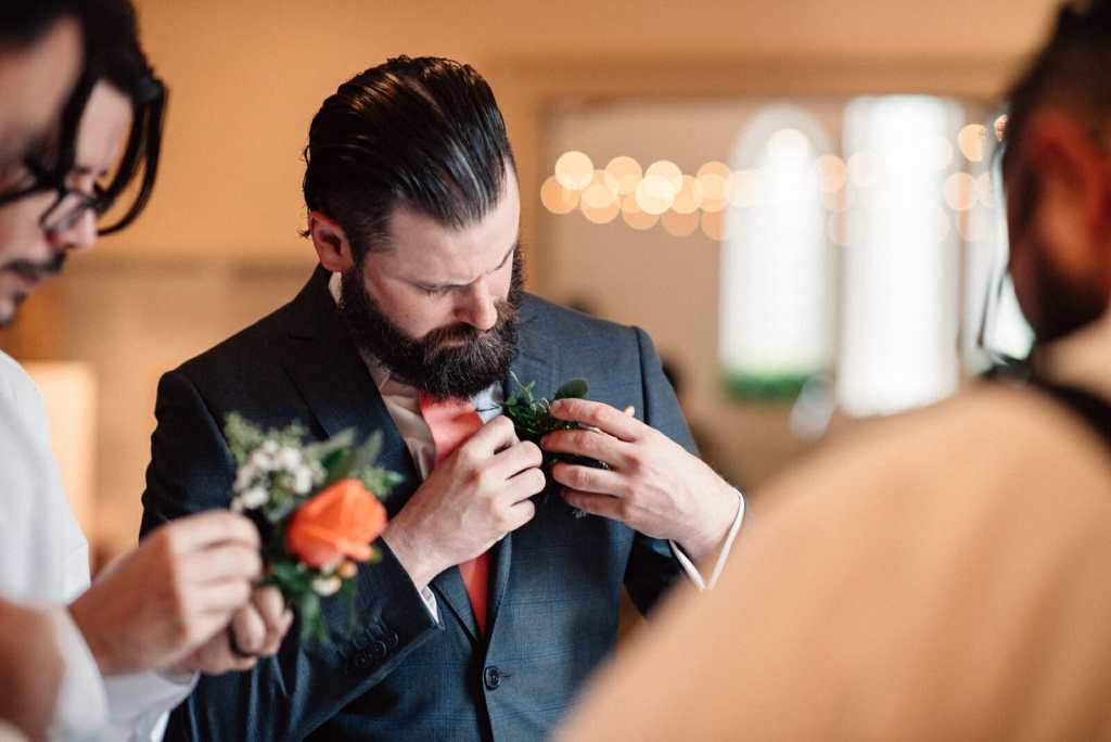 groom putting on his boutonniere at enoch turner