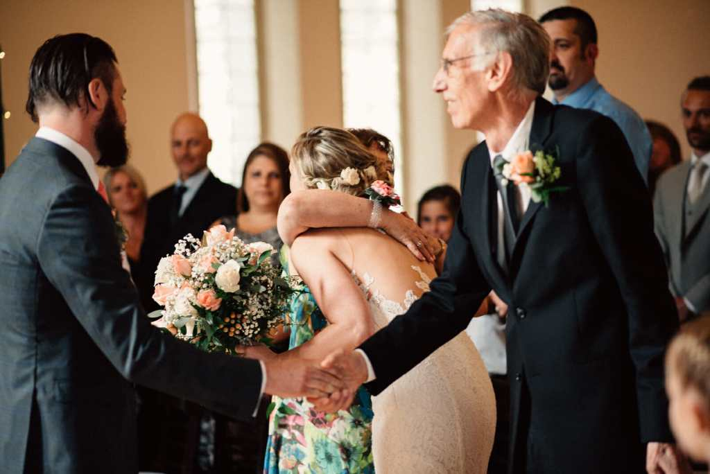 bride hugs mother and groom shakes fathers hand