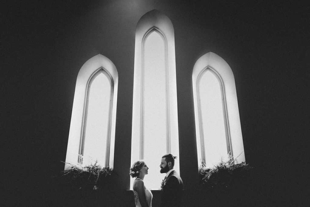 black and white photo of newlyweds in front of gothic window