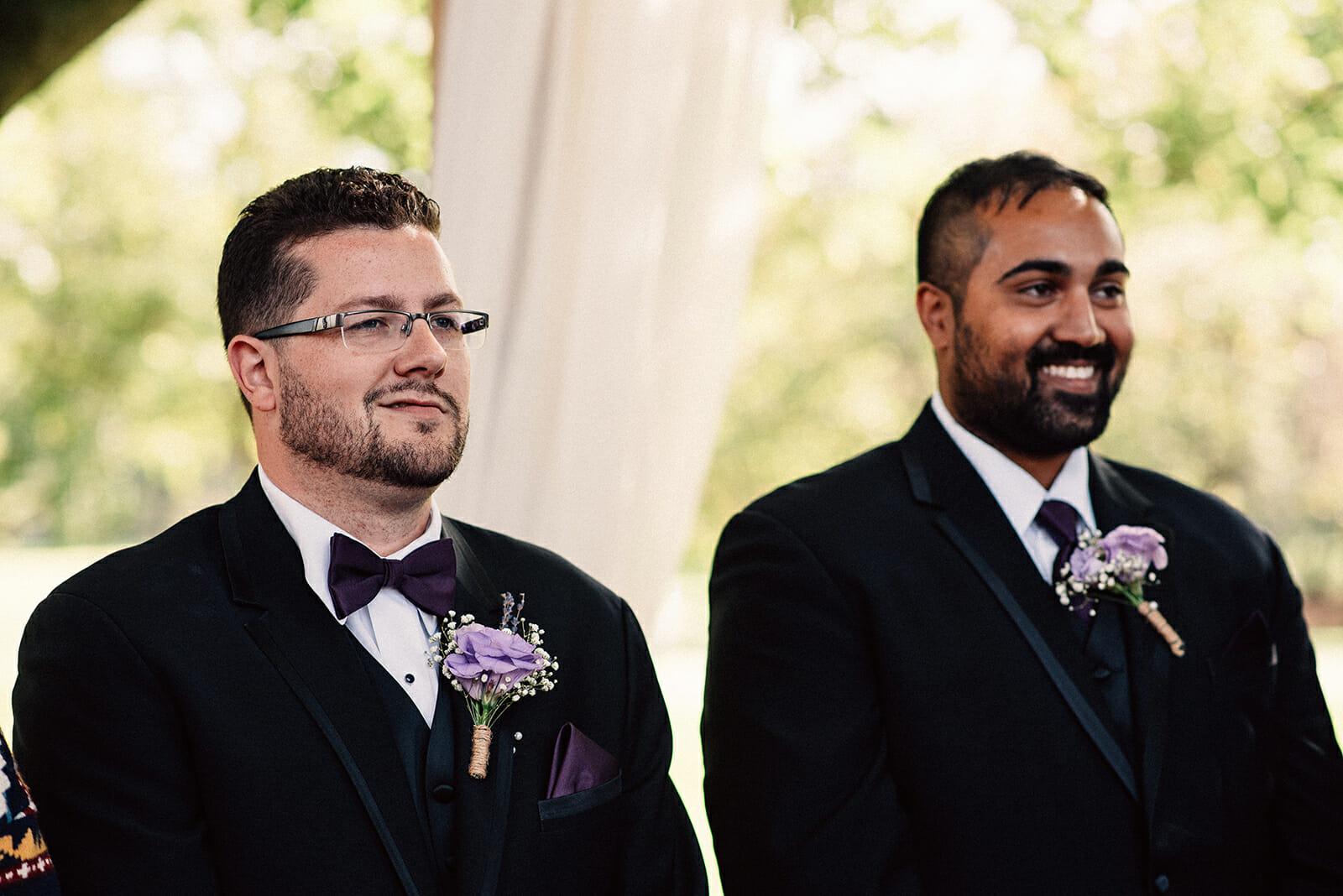 groom smiles while watching bride walk down aisle