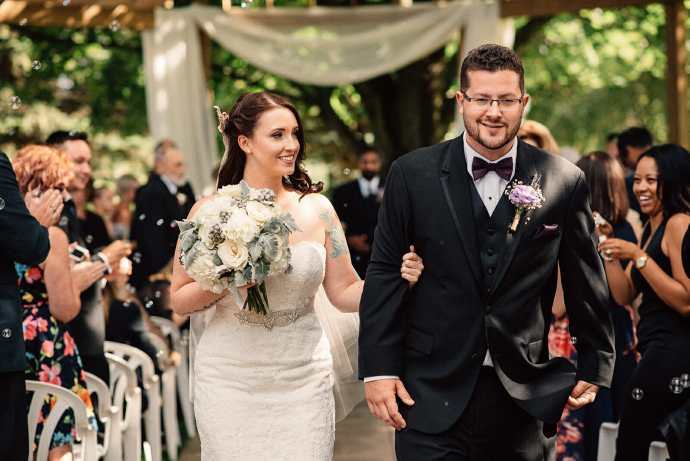 bride and groom walk down the aisle after getting married