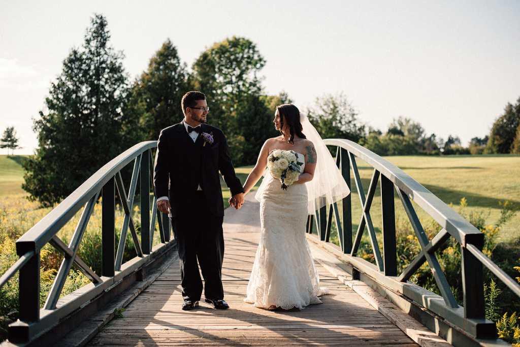 bride and groom walk over bridge holding hands