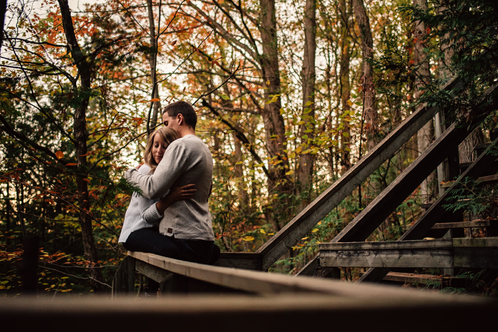engaged couple cuddles on stairs in fall forest